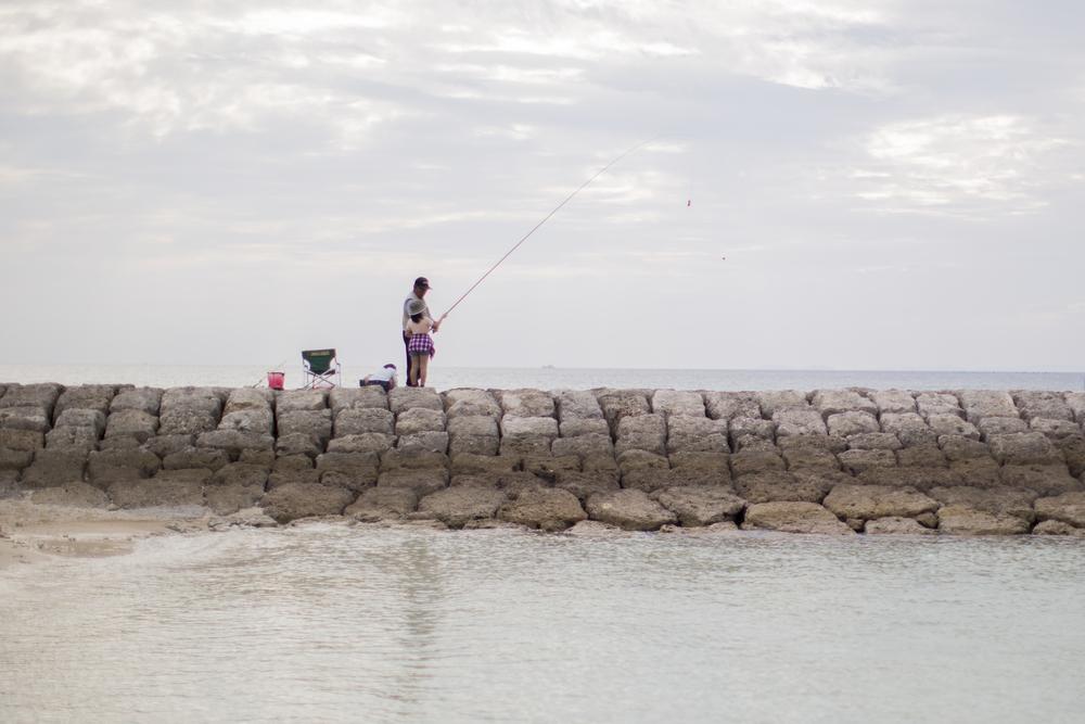 Grandpa teaching her how to fish.