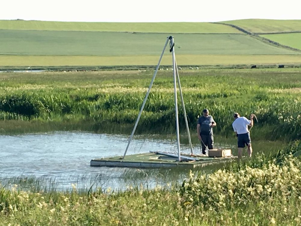 Archaeologists preparing a raft to take cores in the loch of Skaill. This picture also illustrates how different Skara Brae is from the era depicted in  The Boy With The Bronze Axe  . The picture is taken by Sue Dawson and the work is funded by Historic Environment Scotland.