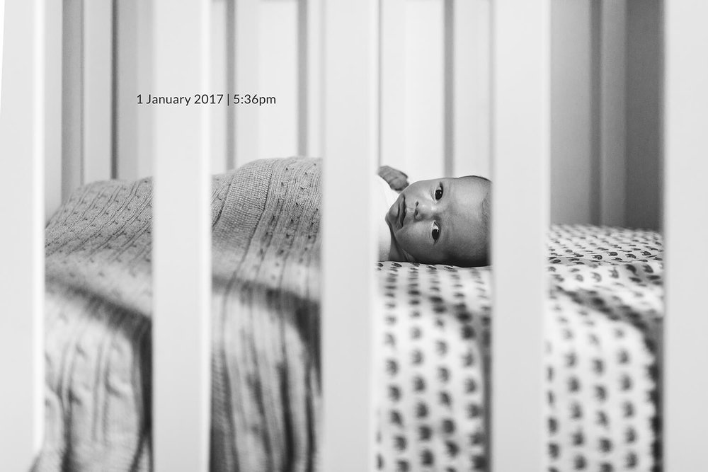 Black and white Melbourne newborn photography of newborn baby in cot.