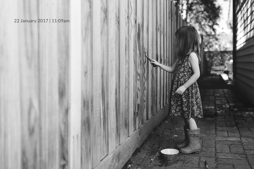 Melbourne family lifestyle photography. Black and white photo of a young girl painting a fence.
