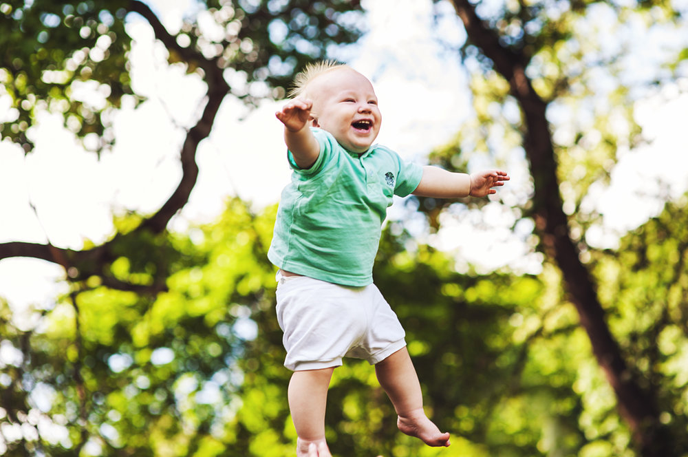 Photograph of a baby boy being thrown in the air