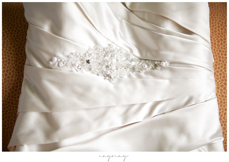 Bridal gown details. White dress made of Satin with pleats