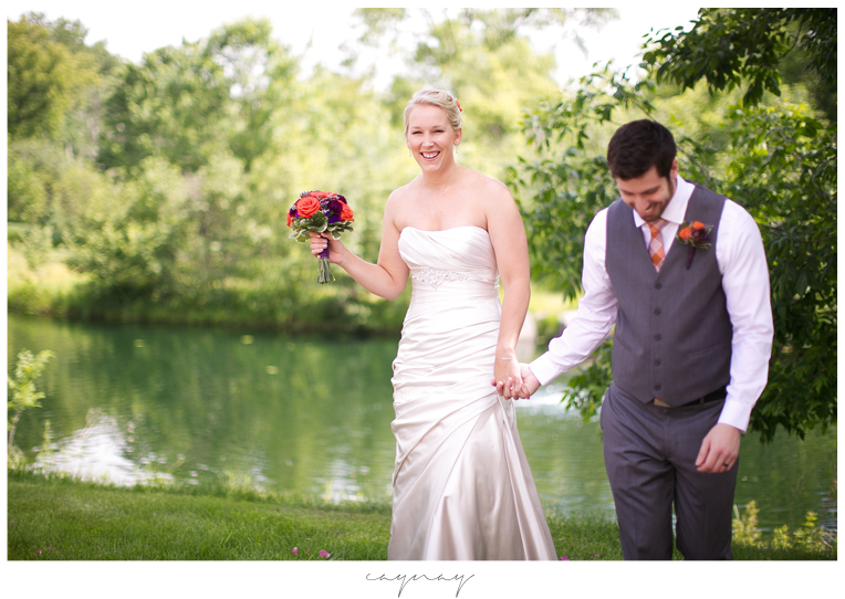 Natural light first look. Groom waiting for bride in front of greenery and pond. Grey tux with orange tie. Purple and orange boutonniere. White dress shirt. Oyster colored satin wedding dress. Orange and purple bridal bouquet.