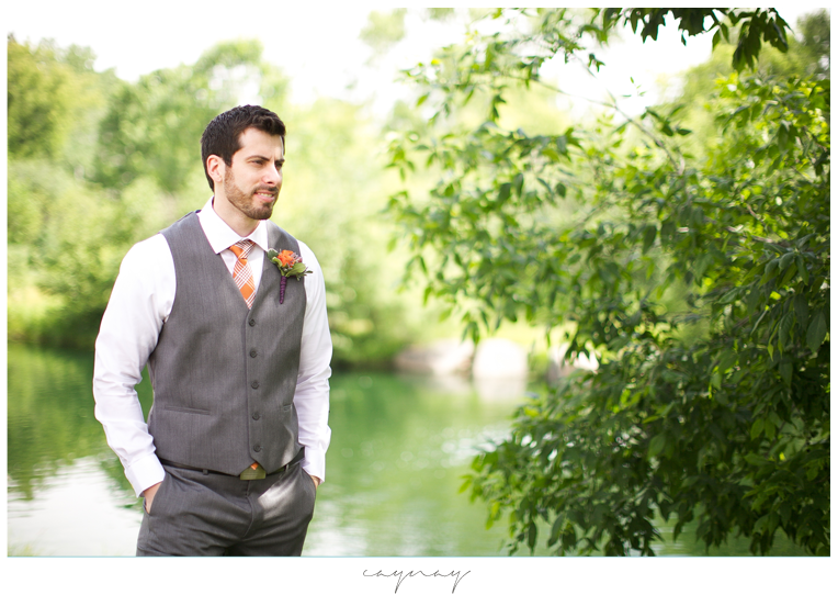 Natural light first look. Groom waiting for bride in front of greenery and pond. Grey tux with orange tie. Purple and orange boutonniere. White dress shirt.