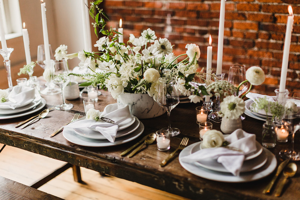 A far from boring decadent white color scheme on our farm tables. Our marble chargers add that touch of modern elagance. Photography  Lady J Memories , styling by  Swoon Event and Design , florals by  The Bend Flower Company , rentals by  Curated .