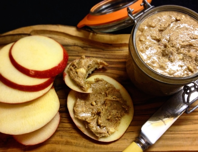 Healthy, homemade snack of dairy free nut butter in a jar with apple slices.