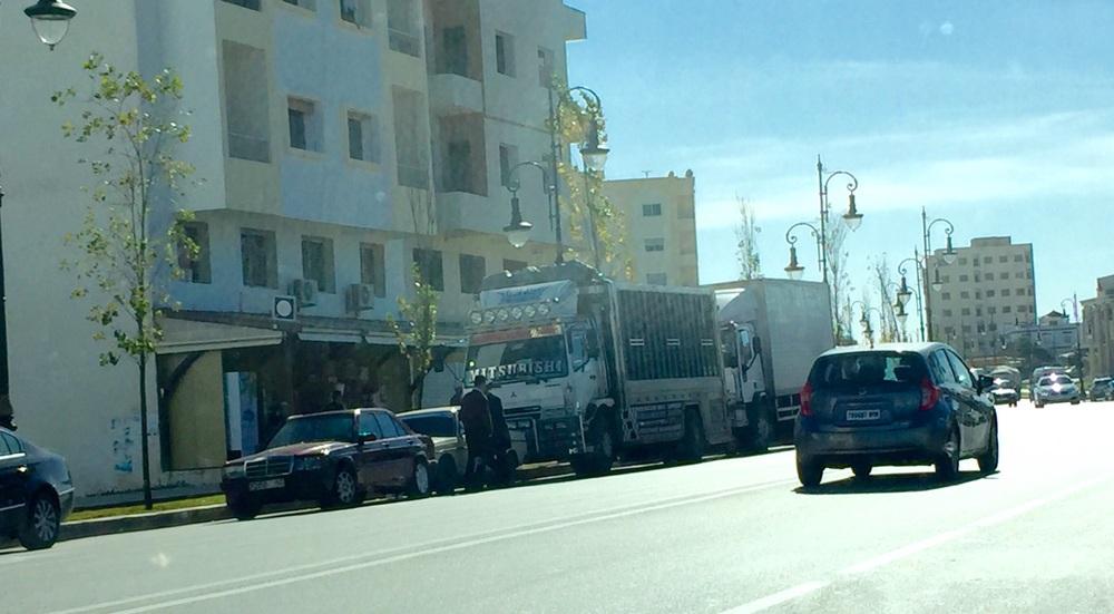 """تظهر في الصورة سيارة مرسيدس """"المقاتلة"""" محاصرة بشاحنة و مرسيدس 190 وامامها عناصر الأمن"""