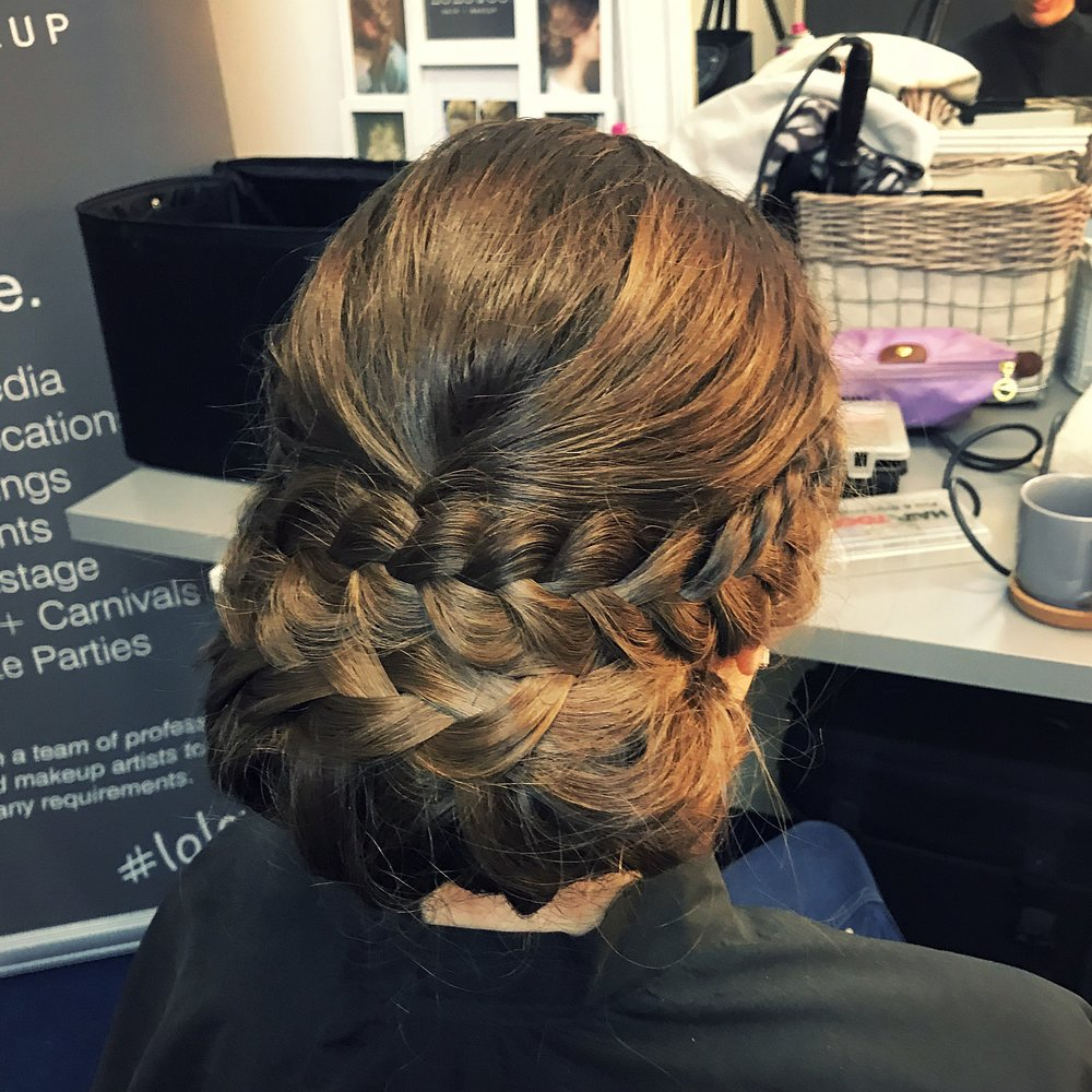 Braided low chignon - A loose elegant chignon at the nape of the neck incorporating a braid into it.