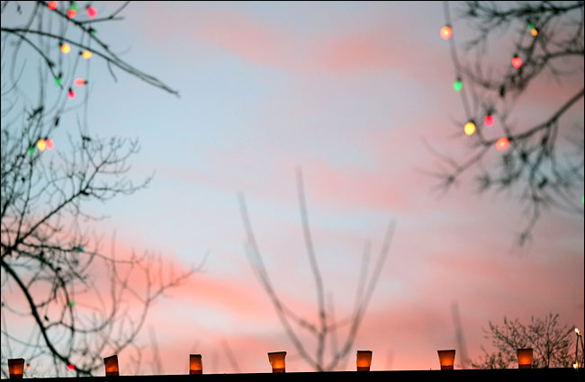 Rick Scibelli Jr. for The New York Times Farolitos, also called luminaries, compete with the setting sun in Santa Fe, N.M.