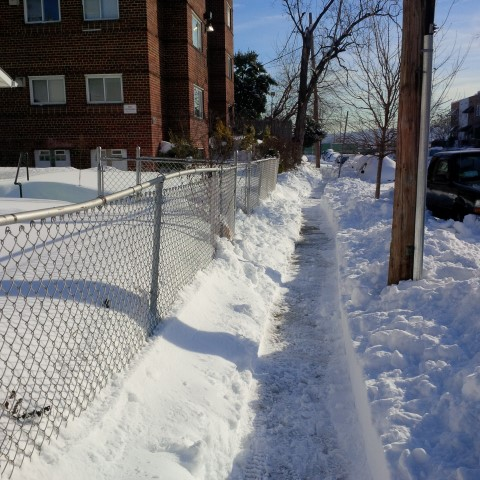 A clear but narrow and icy path along a long stretch of the 1500 block of K St SE.