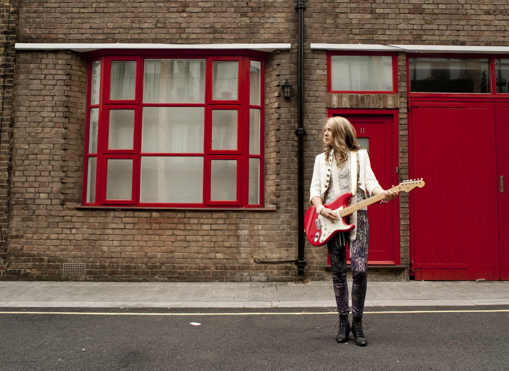 Beatie Wolfe - Standing by red door - photo by Stu Nicholls.jpg