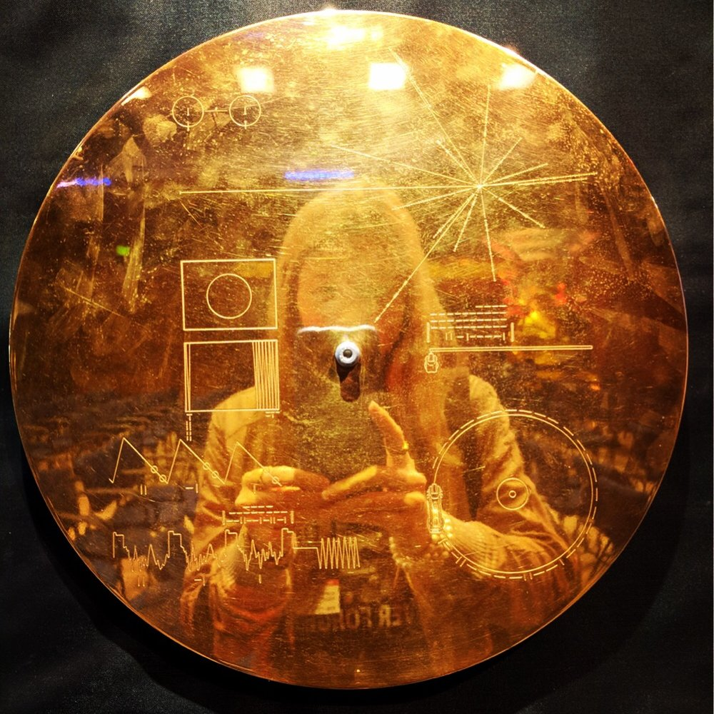 """Beatie Wolfe reflected in """"The Golden Record"""" cover at NASA's JPL"""