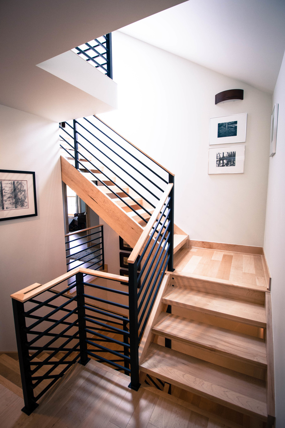 Sleek and clean powder coated steel railing combined with natural maple hand rails help to preserve and accentuate the modern styling present in and