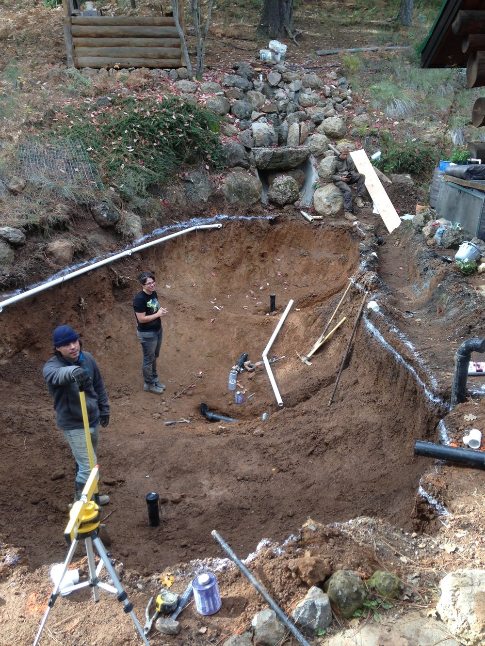 Zach Wollert and Shasta Krueger prepping the 10,000 gallon Koi pond and aquaponic garden for rebar intallation