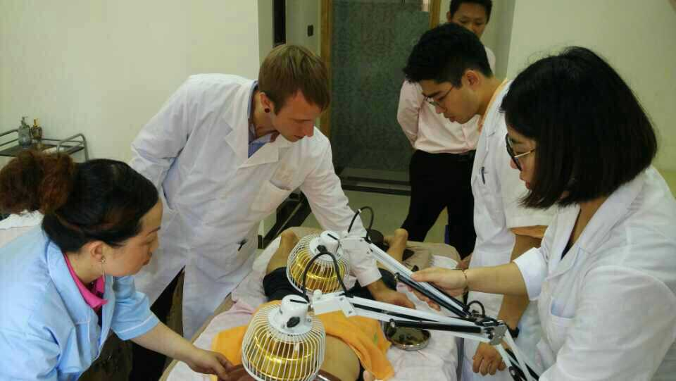 Treating a patient in Xuwen, China with clinic aides assisting and M.Sc students.