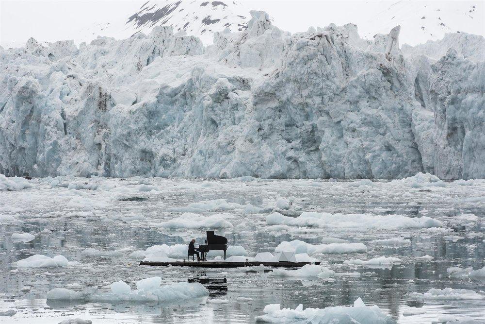 """Un piano flotante Ludovico Einaudi interpreta una pieza con un piano de cola y sobre una plataforma flotante. """"Tenemos que entender la importancia del Ártico, hay que detener su proceso de destrucción y protegerlo"""", expresa el compositor y pianista italiano. Foto: Pedro Armestre / Greenpeace 2016 ( fuente:https://goo.gl/U8EWBt)"""