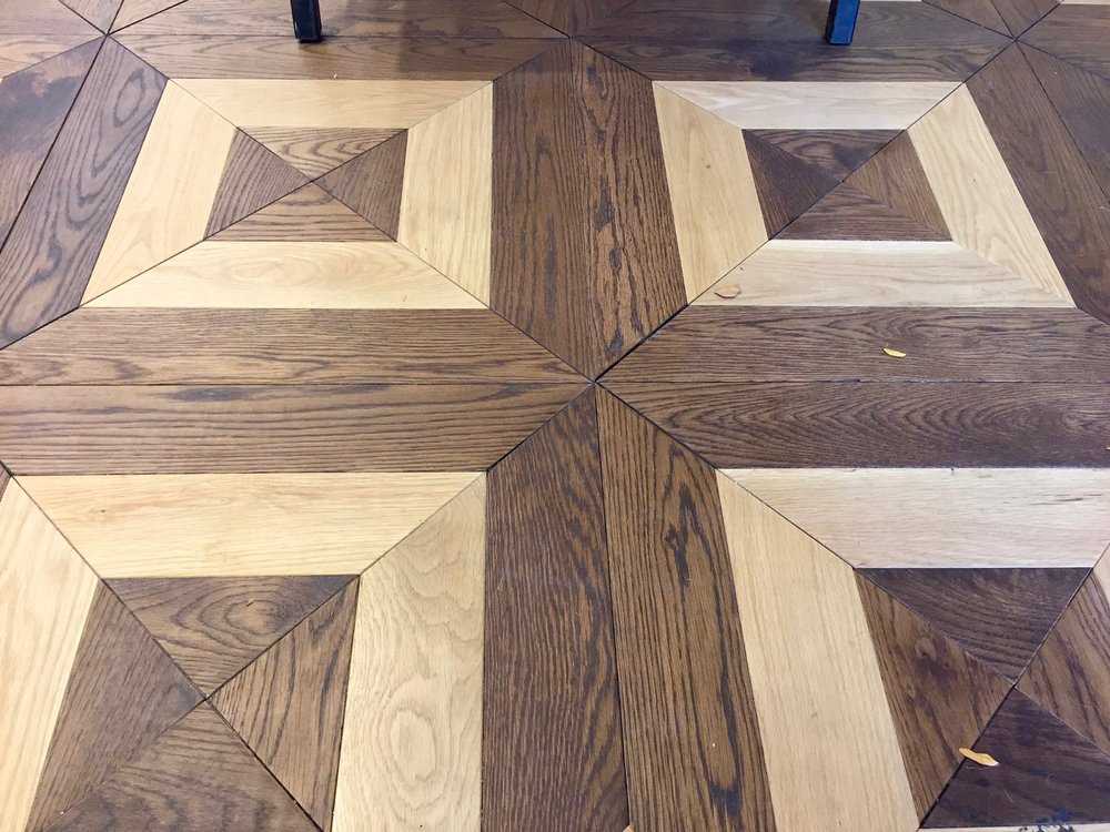 Detail of the store's custom White Oak parquet flooring design.