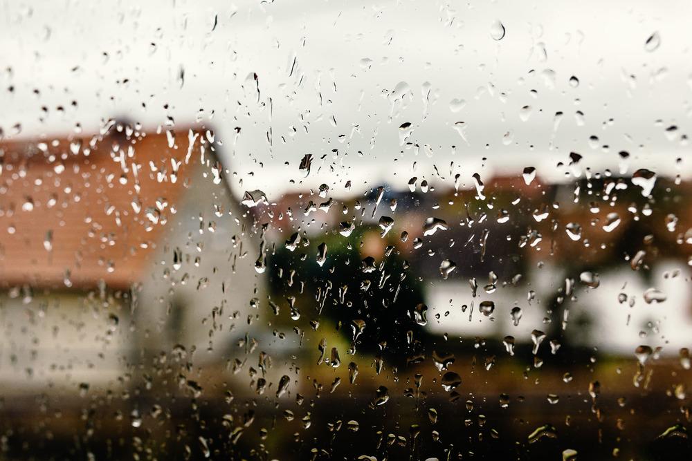 Regentropfen an der Fensterscheibe an einem Regentag