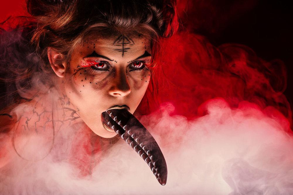 Aktmodel mit Teufelszunge im Mund im Nebel