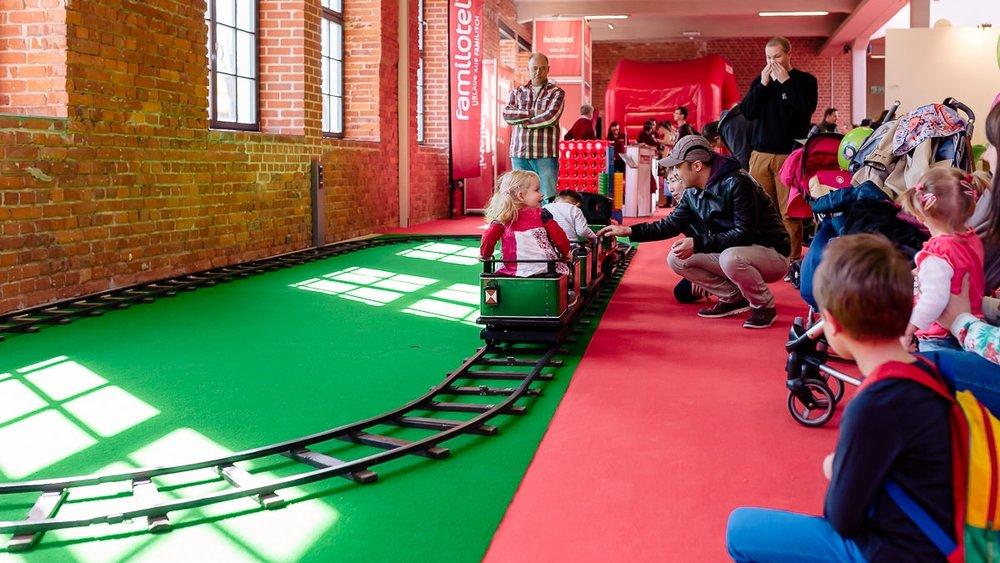 Kinder fahren mit Eisenbahn auf der Babymesse Dresden