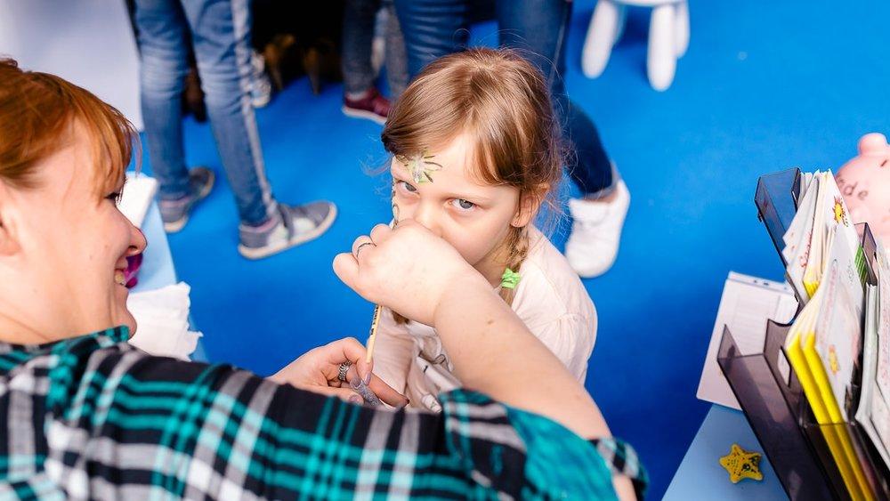 Kind wird beim Kinderschminken auf der Babywelt Messe Dresden geschminkt