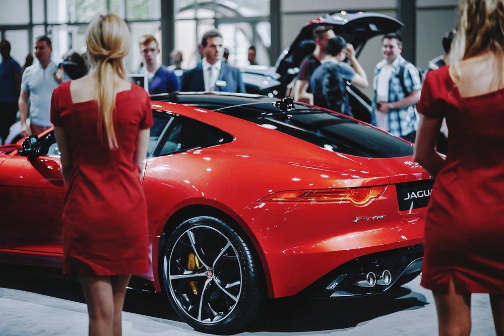 Roter Jaguar mit Messe-Hostessen auf der AMI Leipzig Automesse