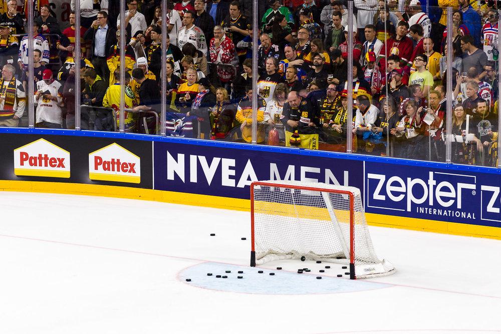 leeres Eishockey Tor mit vielen Pucks