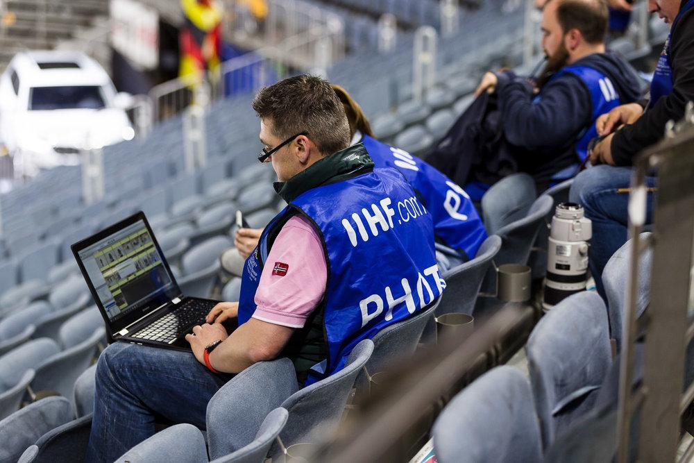 Pressefotografen am Laptop nach dem Eishockey Spiel