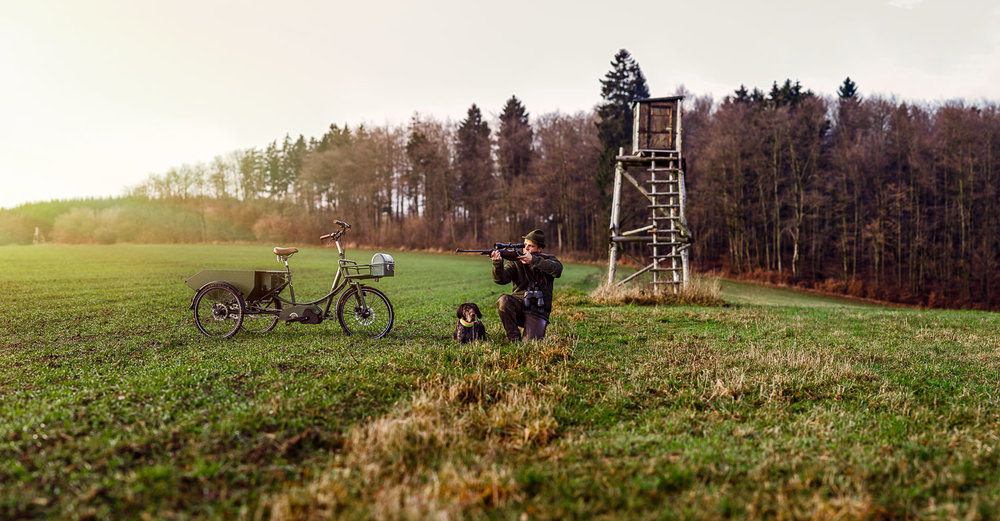 Imagebild Jaeger mit Gewehr im Anschlag neben Jagdhund und Jagdrad | Fotograf Peter Meyer pm-modus.com