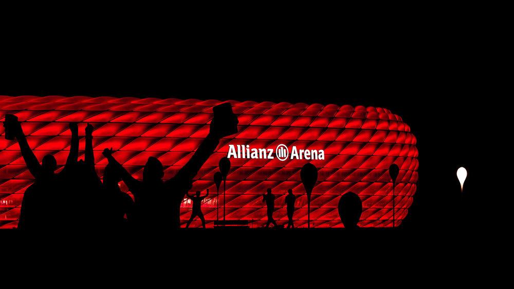 Die rot beleuchtete Allianz-Arena in München mit singenden Fans als Silhouetten im Vordergrund | Foto: Peter Meyer www.pm-modus.com
