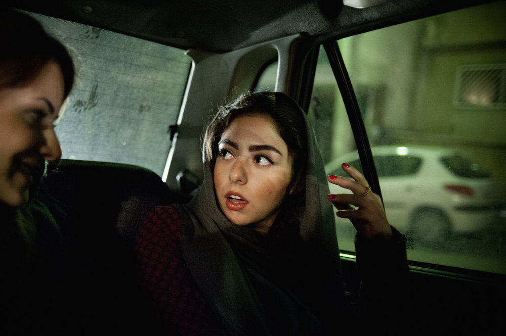 THERAN, IRAN: Yassi and her friend on their way to an opening reception at a gallery in North of Tehran. Even though being bold and eye-catching is always a factor that concerns the morality police, many girls choose to put on bright lipstick and wear distinctive fashion.