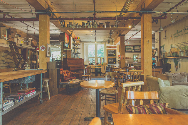 Merchants  on Flickr.   This is the inside of Merchants of Green Coffee. It is not only my closest cafe, but one of my favourites. If you like wooden beams, coffee plants, couches, books, games, coffee and living in Toronto, you should go.