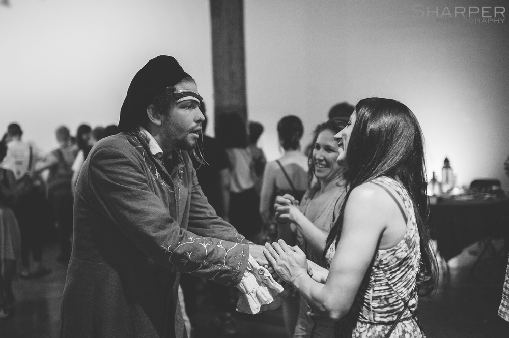 Black and white photo of actor engaging with audience member at immersive theater performance in Austin