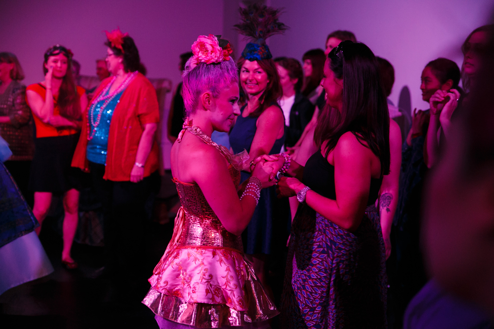 Dancer dressed in Rococo fashion holds hand of audience member during Austin immersive theater show