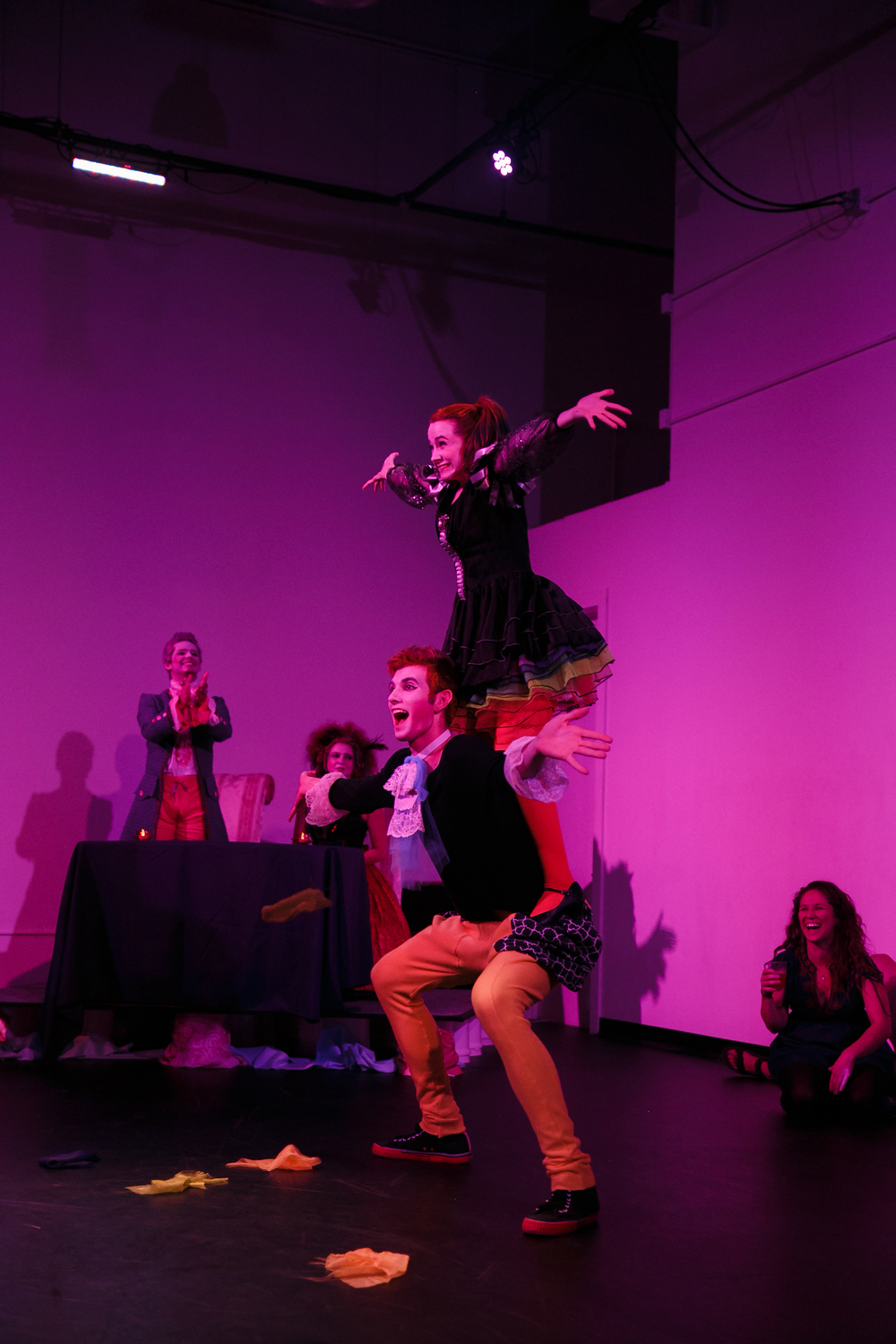 Dancer on top of actor's shoulders performing at Austin dance theater show themed to 1600s Europe