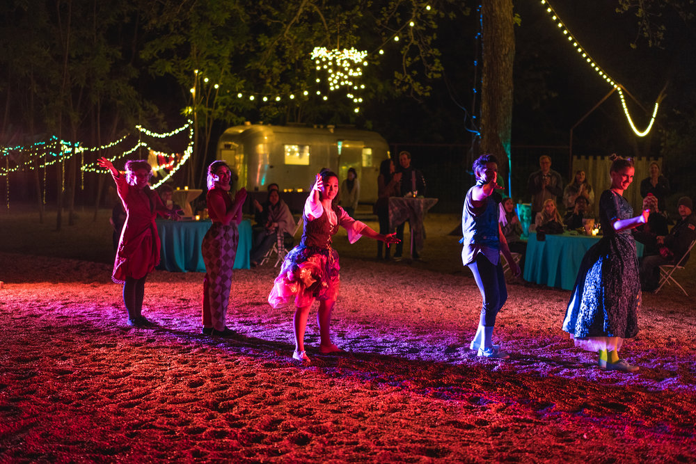 Multiple dancers onstage at outdoors Austin event performance