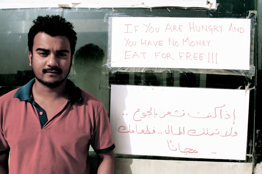 Zaiqa Restaurant manager Birkha from Nepal standing in front of the 'eat for free' sign.