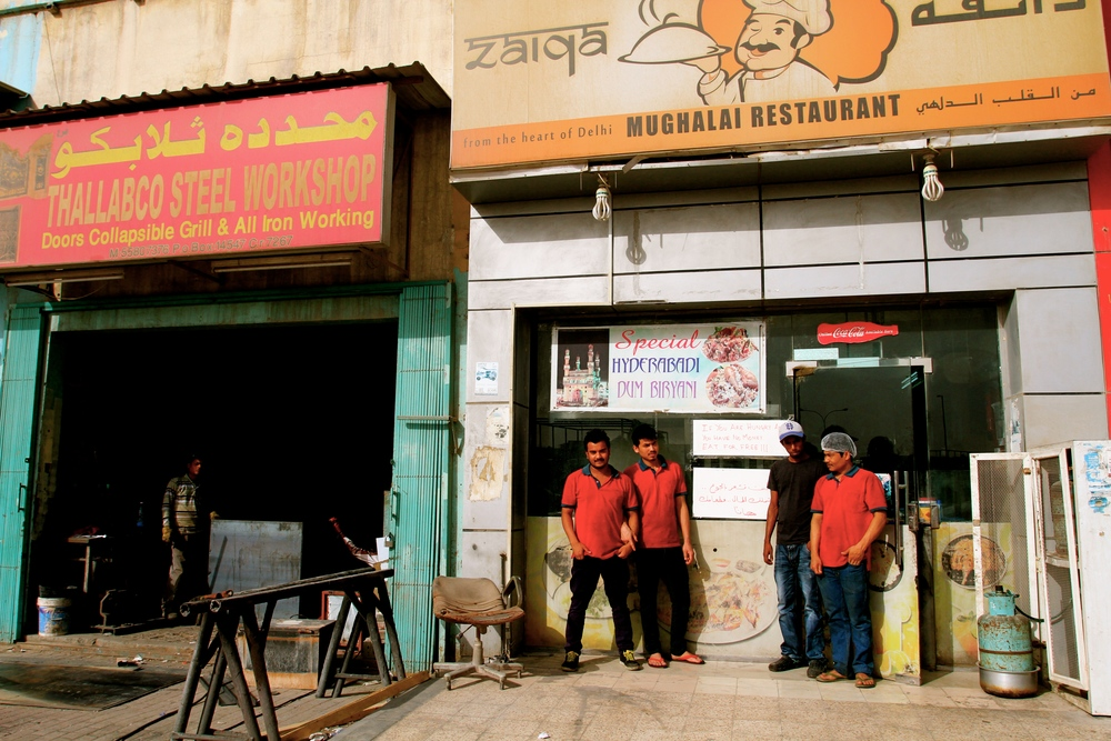 Zaiqa Restaurant staff stand next to the 'eat for free' sign.