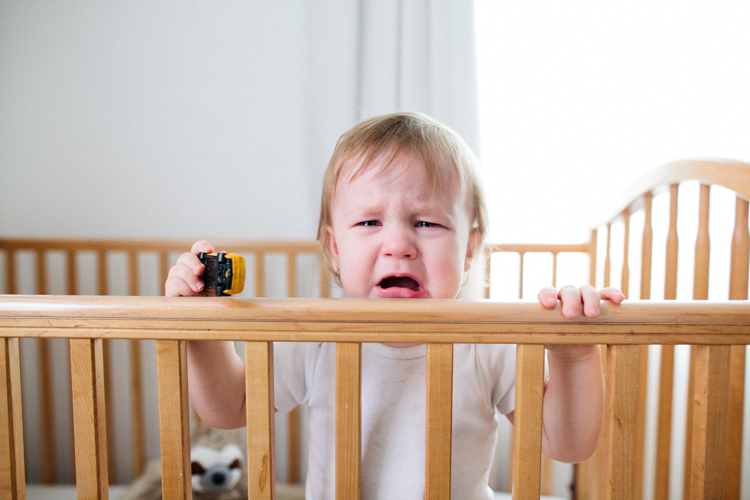 baby-pouting-in-crib-holding-toy.jpg