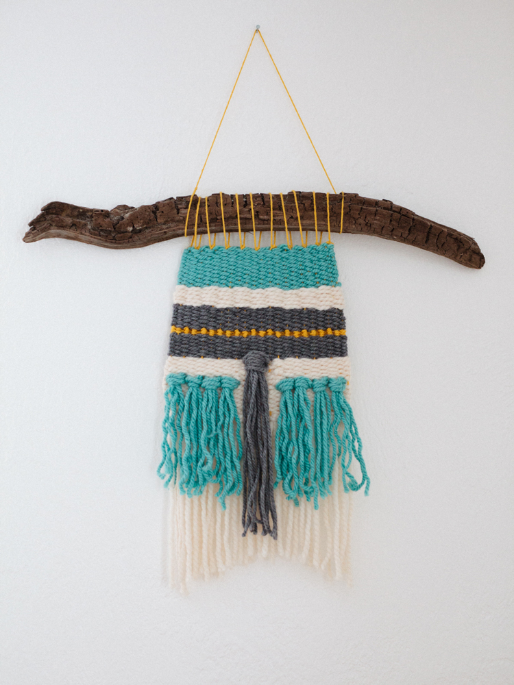 blue-and-gray-yarn-weaving-on-driftwood.jpg