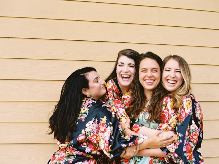 laughing hugging bridesmaids in floral robes