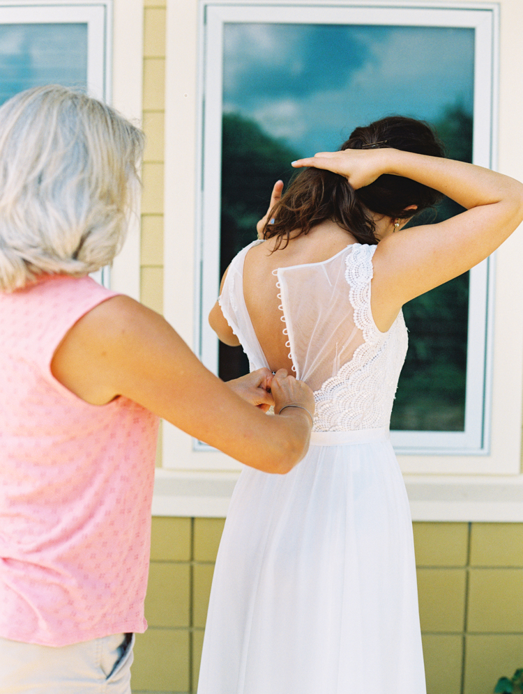 mother buttoning brides dress outside