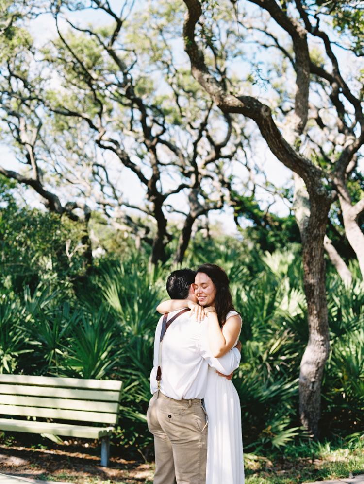 groom and bride hugging under oak trees