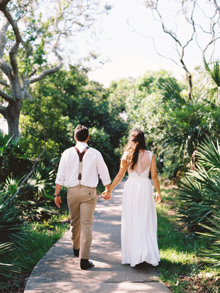 bride and groom walking away down a forest path