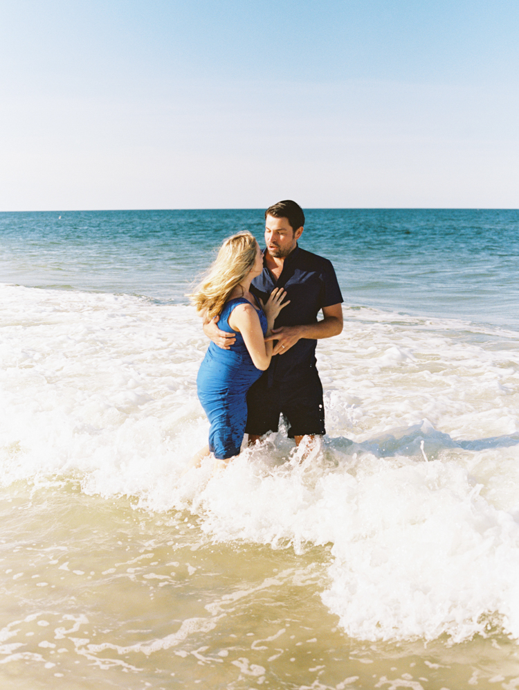 pregnant couple hugging in the ocean