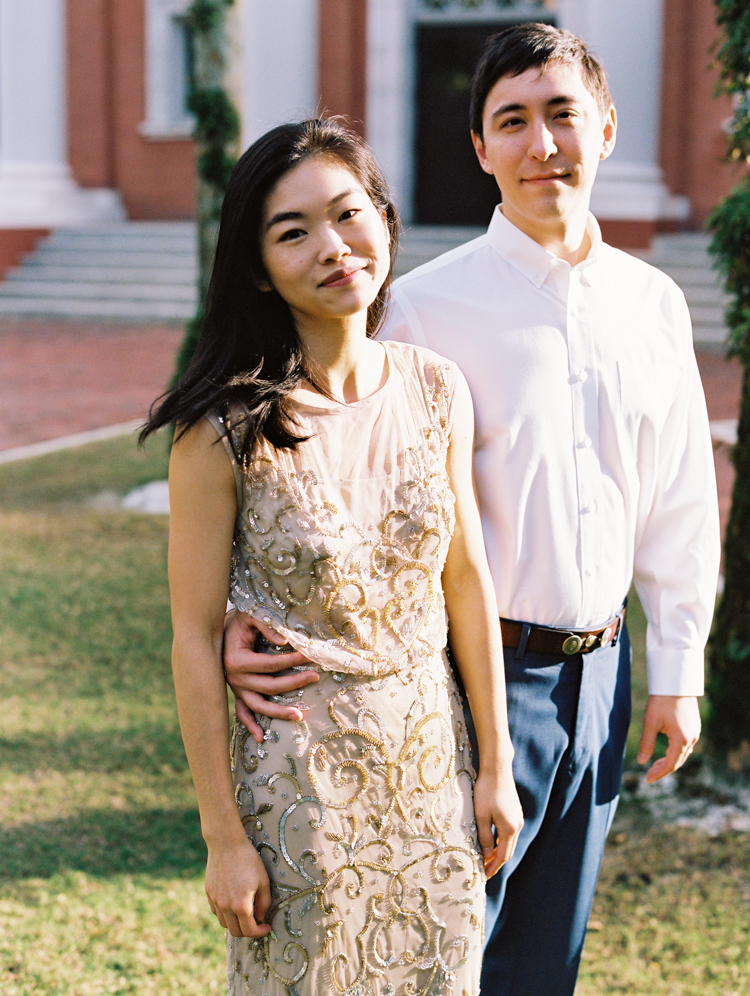 asian woman in champagne evening gown with man's arm around her waist