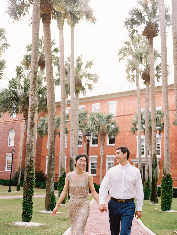 couple walking through palm trees at Stetson University