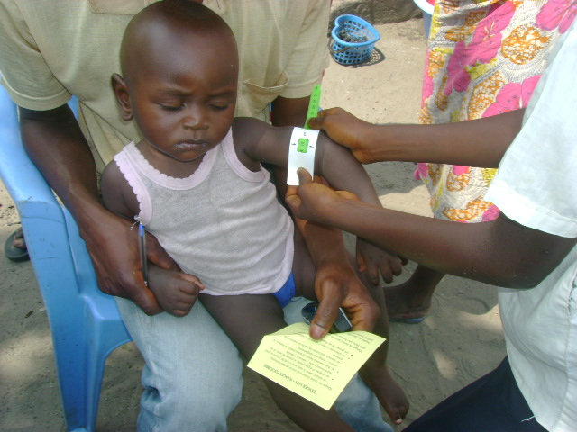 Students measure the arm of a child as an indicator of malnutrition.