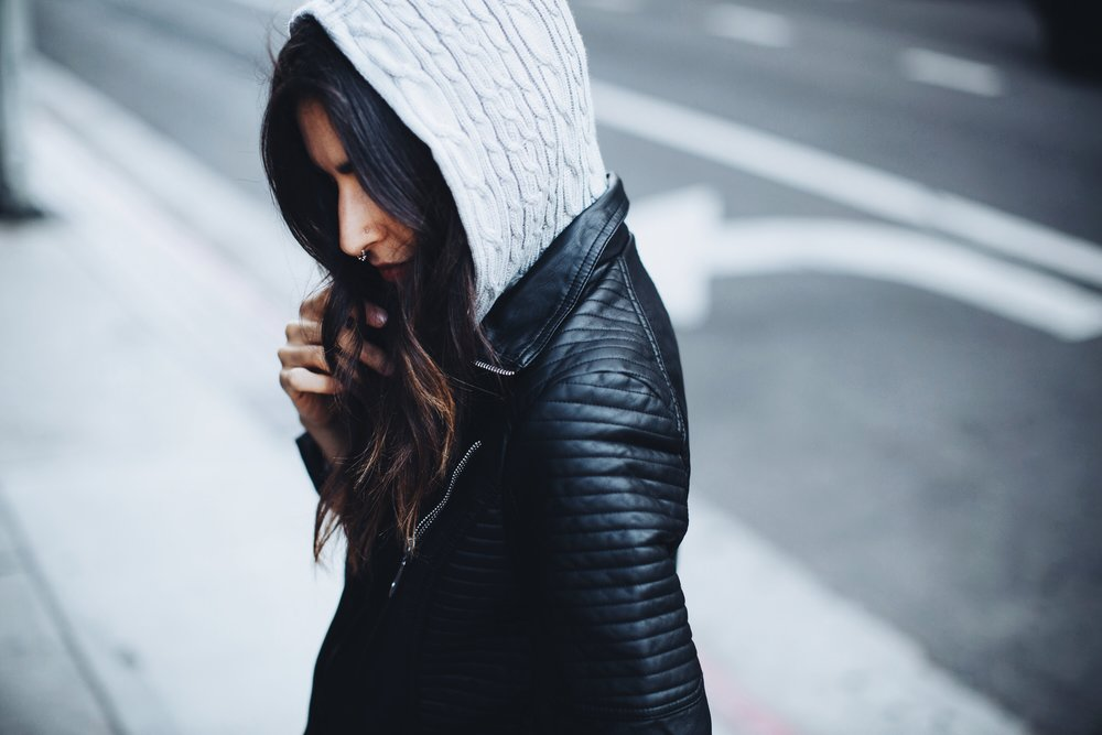 Wearing the leather  jacket  with a detachable sweater hood.