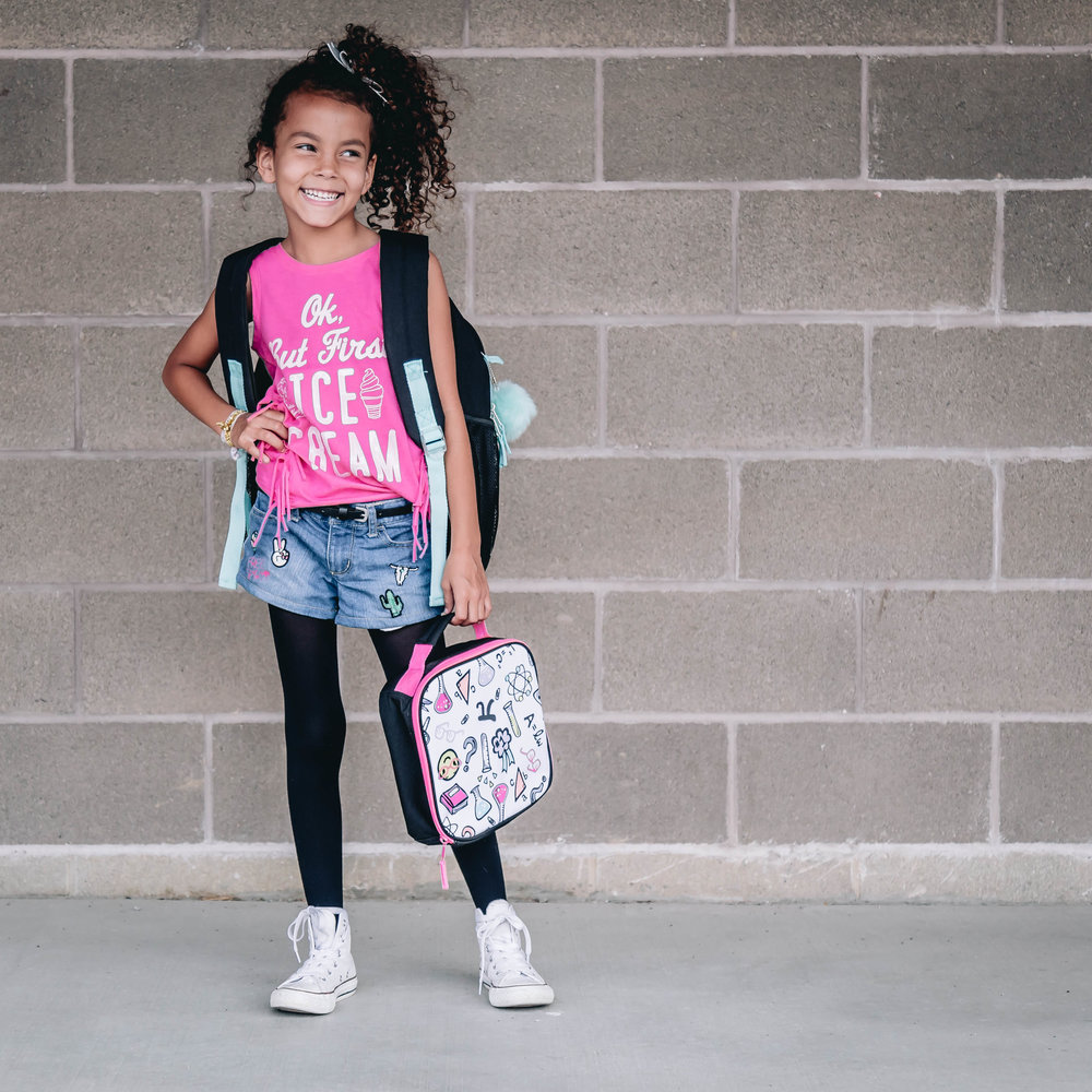 Sporty & Sweet - Can you guess which subjects are this spunky little second grader's favorites? Lunch and recess! Why? Because that is when she can share her favorite sweet treats and then catch up on chatting with friends! She is dressed for all things sporty in her bright pink fringe top and patched jean shorts. And don't forget that rad new lunch box! The only time you'll find this energetic girl sitting down is on the swings! #youCANsitwithus